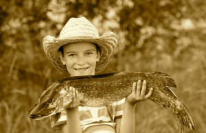 Boy holds big pike he just caught