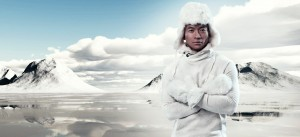 Asian winter fashion man in snow mountain landscape. Wearing white hoody sweater with furry hat and gloves.