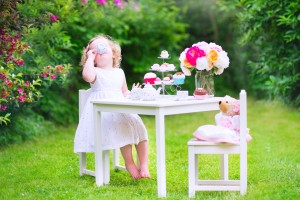 Toddler girl playing tea party with a doll